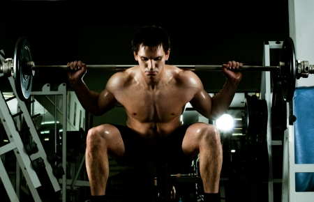 vigorously: very power athletic guy ,  execute exercise with  dumbbells, in  sport-hall Stock Photo