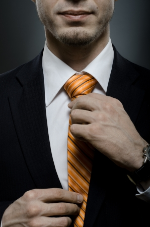 exacting: portrait  the  beautiful  businessman  in black costume tie ones necktie  Stock Photo