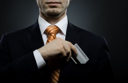 take out: businessman in black costume and orange necktie put or take out credit card in pocket, close up Stock Photo