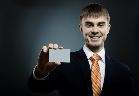businessman  reach out on camera and show credit card or visiting card, smile Stock Photo - 14609073