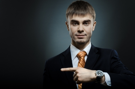 businessman index finger point sideways, on dark grey background, horizontal photo Stock Photo - 14609082