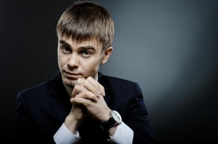 pensiveness: il ritratto del giovane imprenditore in costume, sguardo fisso, su sfondo blu scuro