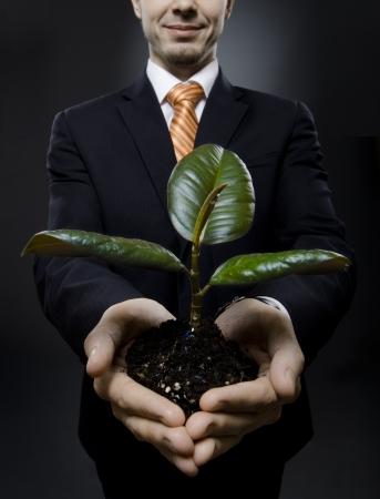 solicitous: vertical photo  businessman in black costume with  scion  rubber plant