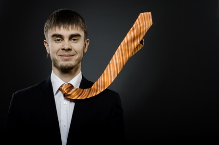 potentiality: portrait  the  beautiful  businessman careerist in black costume and orange necktie Stock Photo
