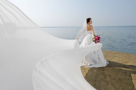 beautiful fiancee in white wedding dress and big long white train, stand on shore sea