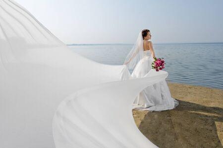 bröllop: vackra fästmö i vit brudklänning och stora långa vita tåg, stå på land hav Stockfoto