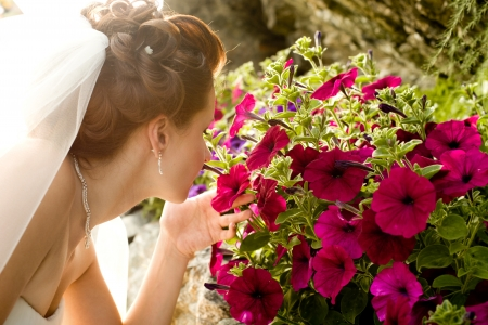 fiancee: horizontal wedding portrait beautifull  fiancee smelled  beauty flowerbed of red-lilac-coloured flowers,  outdoor