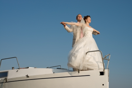 newly married couple stand on nose white yacht, on sky background photo