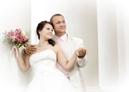 happy newly married couple in white dress, smile and cuddling, outdoor photo