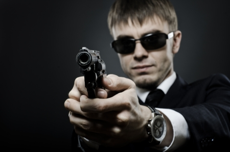 felon: portrait  the  beautiful  man in black costume,  special-service agent or  body guard with  pistol Stock Photo