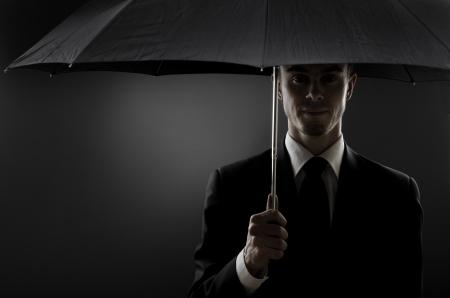 undercover: Uomo del ritratto l'uomo bello in costume nero con ombrello blak, speciale servizio di agente o guardia del corpo Archivio Fotografico