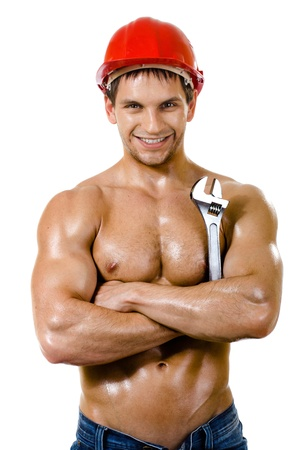 constructors:  the beauty muscular worker  man, in  safety helmet  with big wrench  in hands, turn on and smile, on white background, isolated Stock Photo