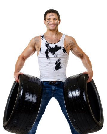 brawny: the very muscular handsome sexy guy hold rubber-tire and white,  on  white background, isolated
