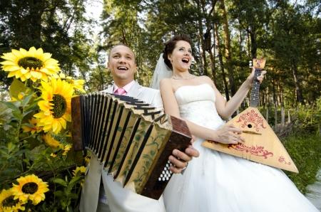merrymaking: happy newly married couple play on accordion and   balalaika, wedding  humour photo