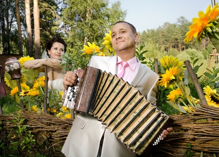 happy newly married couple,  bridegroom  play on accordion , wedding  humour photo photo