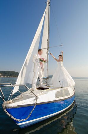 merriment: vertical photo  newly married couple stand on  white yacht, outdoor Stock Photo