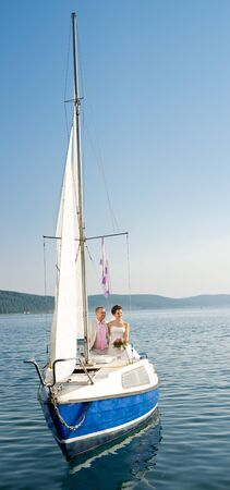 pleasure boat: vertical photo  newly married couple stand on  white yacht, outdoor Stock Photo