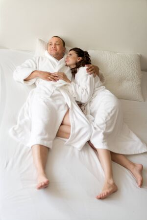 bedstead: happy couple lie together in  bedstead on white bed,  morning wake up and embrace Stock Photo