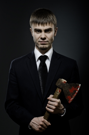 portrait  the   businessman  in black costume and black necktie with axe, sinister look  photo