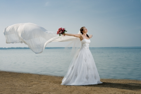 약혼녀: 흰색 웨딩 드레스와 큰 긴 흰색 기차에서 아름다운 약혼녀, 해안 바다에 서 스톡 사진
