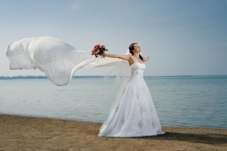 fiancee: beautiful fiancee in white wedding dress and big long white train, stand on shore sea