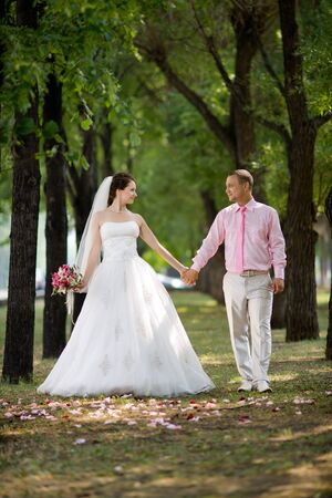 happy newly married couple in white dress, romance walk to  wood photo