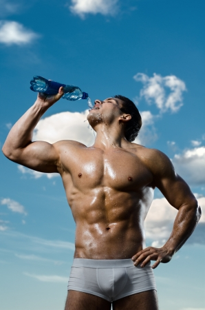 the very muscular handsome sexy guy on sky background, drink water, focus on face photo