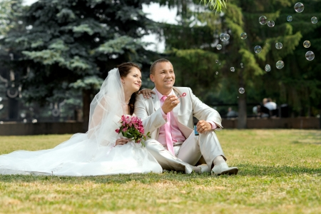 cutie happy married  couple  on nature in park ,  play with soap-bubble and joy smile Stock Photo - 14627937