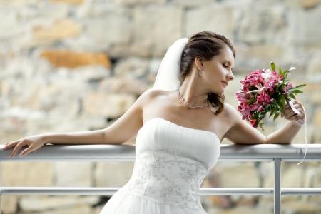 fiancee: horizontal wedding portrait beautifull  fiancee with  bouquet  in white dress, soft light Stock Photo