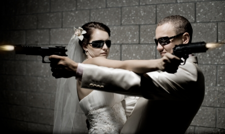 male killer: newly married couple in white wedding dress, shoot of  black pistols Stock Photo