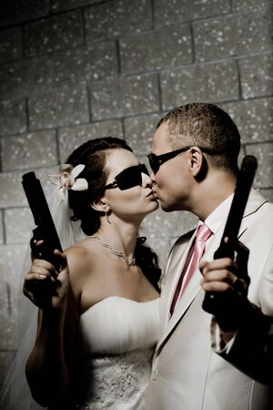 newly married couple in white wedding dress, kiss with  black pistols photo