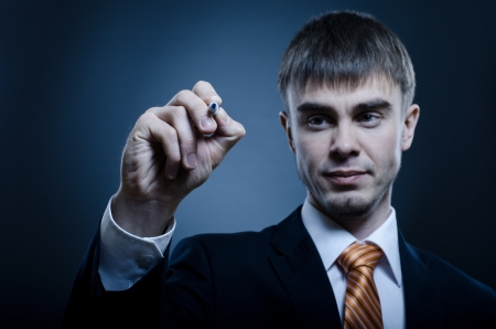 likeness: portrait  the  beautiful  businessman in  costume, hold marker in hand and write on camera, blue light Stock Photo