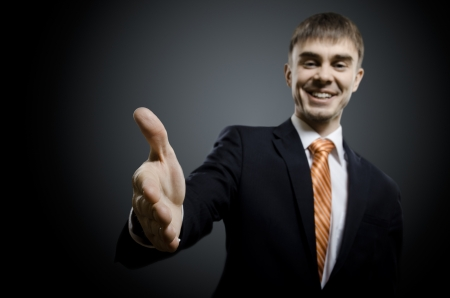 affability: portrait  the  beautiful  businessman in black costume and orange necktie reach out  hand for handshake Stock Photo