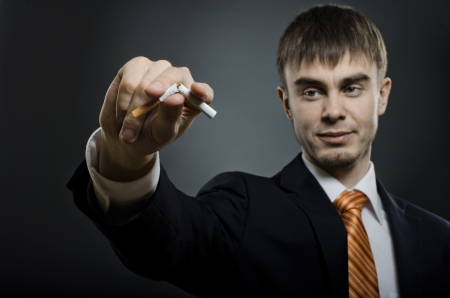 portrait  the   businessman in costume give up cigarette. no smoking - concept photo