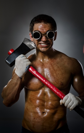 vertical photo crazy frenzied chopper  butcher man  on dark grey background,  action with big axe
