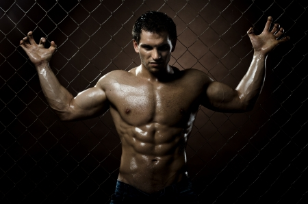 torture: the very muscular handsome sexy guy ,  on  netting   steel fence Stock Photo