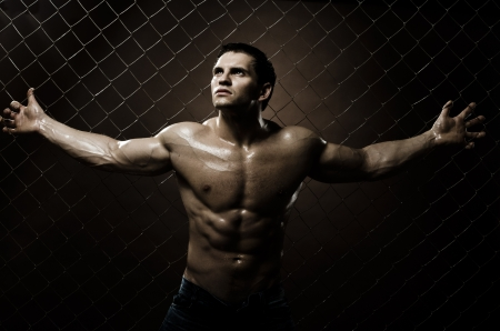 the very muscular handsome sexy guy ,  on  netting   steel fence photo