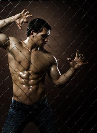 netting: de zeer gespierde knappe sexy kerel, betreffende de saldering stalen hek