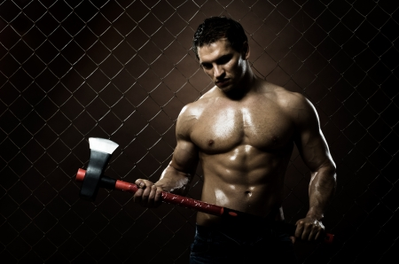 murdering: the very muscular guy on dark  brown netting background  with big axe  Stock Photo
