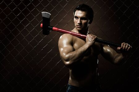 malefactor: the very muscular guy on dark  brown netting background  with big axe  Stock Photo