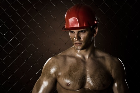 miry:  the beauty muscular worker  man, in  safety helmet , on netting fence background