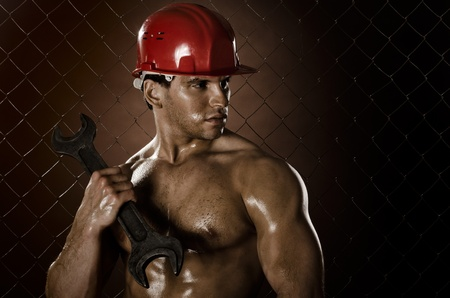 miry:  muscular worker man, in  safety helmet  with big wrench  in hands, on netting fence background Stock Photo