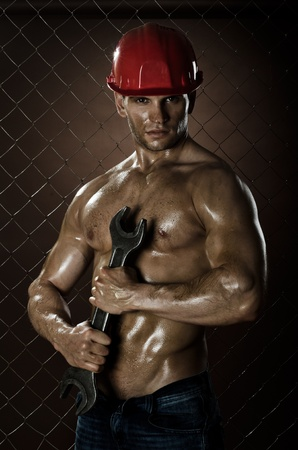 muscular worker man, in  safety helmet  with big wrench  in hands, on netting fence background photo