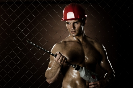 perforator: the beauty muscular worker driller man ,  hold  big perforator in hand, vertical photo