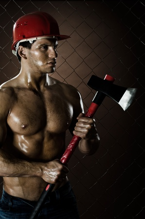 miry: the beauty muscular worker  chopper  man, in  safety helmet  with big  heavy ax  in hands,  on netting fence background