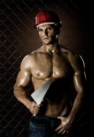 the  muscular worker  man, in  safety helmet  with trowel in hand, on netting fence background photo