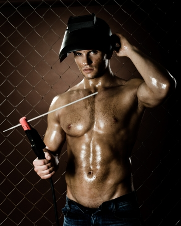 muscularity: the muscular worker welder  man, weld  electric arc-weld, on netting fence background