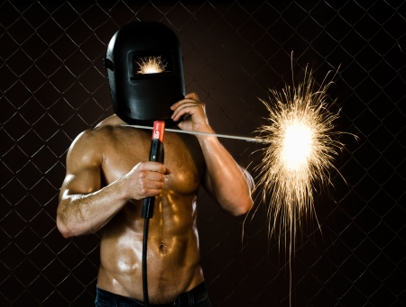 workman:  the beauty muscular worker welder  man, weld  electric arc-weld, on netting fence background