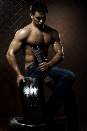 the very muscular workman with rubber-tire and big wrench,  on  netting  steel fence background photo
