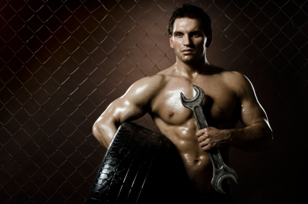 the very muscular workman with rubber-tire and big wrench,  on  netting  steel fence background